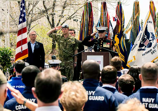 Prince Harry (in camouflage) salutes during the opening ceremony of the Warrior Games.