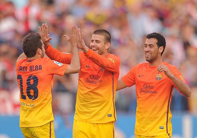 Jordi Alba, Gerard Pique (center) and Sergio Busquets celebrate Barca's win over Atletico Madrid.