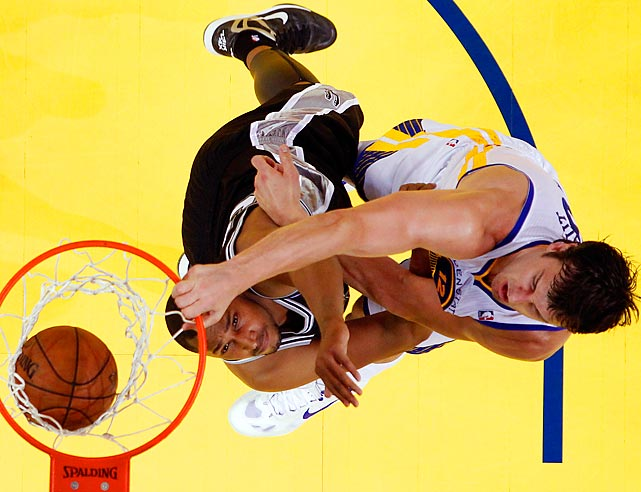 The Warriors' Andrew Bogut (right) dunks over the Spurs' Boris Diaw during Game 3 on Friday.