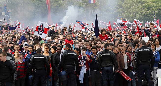 Supporters of Paris Saint-Germain wait for their team as they celebrate winning the French league title.
