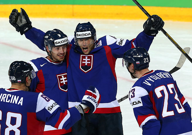 Roman Kukumberg (arms raised) celebrates with his teammates after Slovakia's third goal.