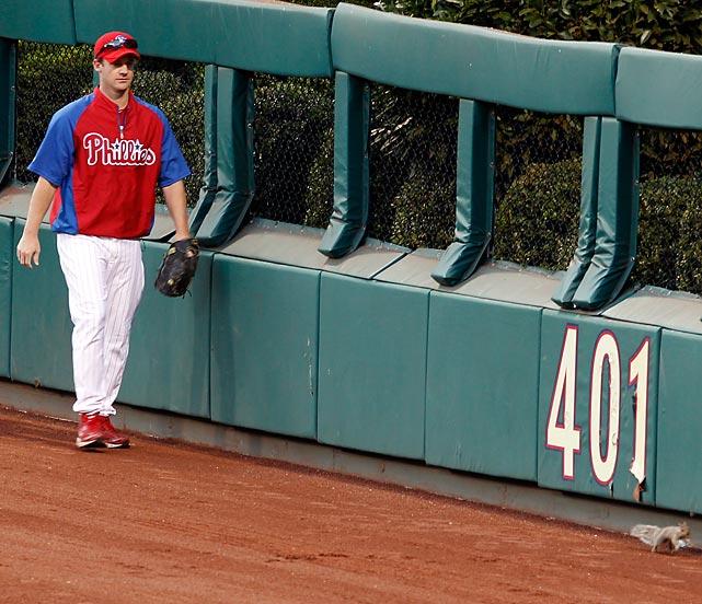 Phillies pitcher Roy Oswalt walks behind a squirrel in Philadelphia.