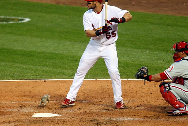 A squirrel crosses home plate in front of Skip Schumaker and Phillies catcher Carlos Ruiz at Busch Stadium in St. Louis.