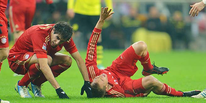 Bayern's Holger Badstuber lies injured during a match with Dortmund in December.