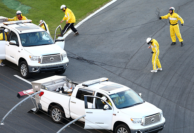 Track workers cleaned up a TV cable that landed on the track at Charlotte, causing a delay in the race.