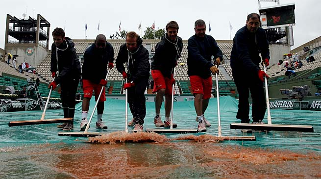 Rain is cleared from Suzanne Lenglen Court on Tuesday.