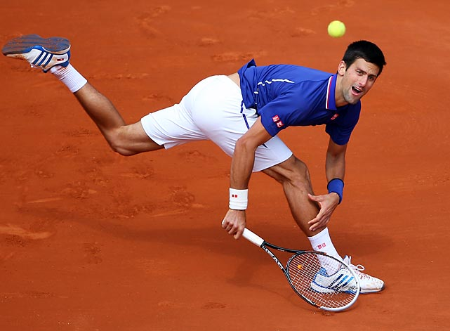 Novak Djokovic of Serbia plays a backhand return in his match against Philipp Kohlschreiber of Germany in a Day 9 victory June 3.