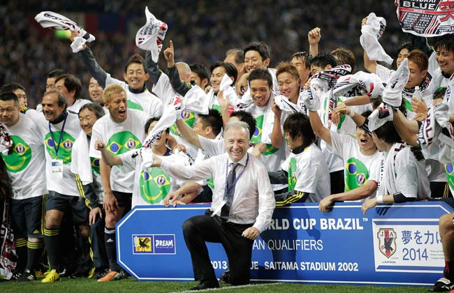 Japan's head coach Alberto Zaccheroni celebrates with his team after securing World Cup qualification