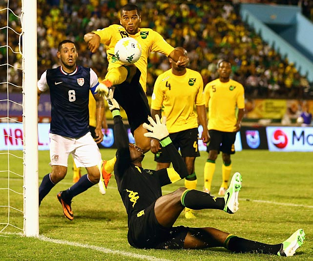Clint Dempsey watches as Donovan Ricketts (1) and Adrian Mariappa (19) try to stop a shot at the goal.