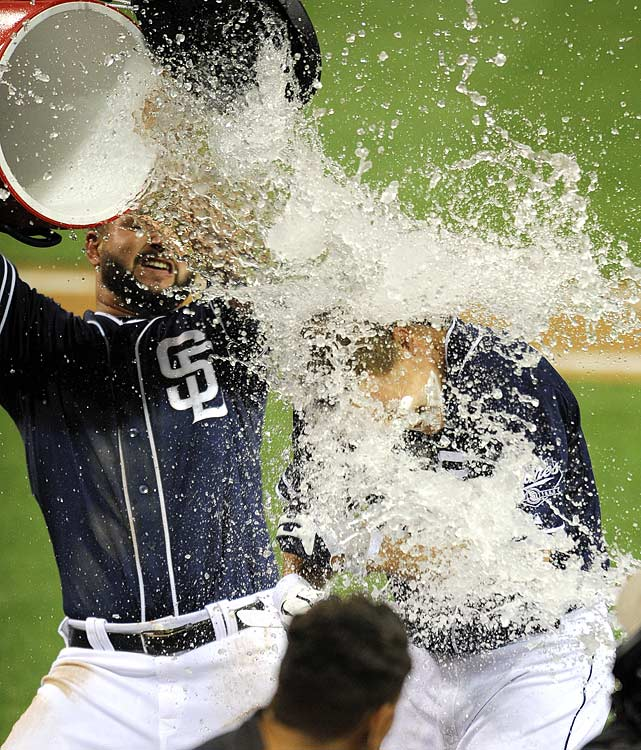 Nick Hundley is doused by teammate Yonder Alonso following the Padres 8-7 win over the Giants. Hundley drove in the game-winning run in the 12th inning.