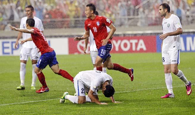 Uzbekistan's Shorakhmedov Akmal (bottom) reacts after giving up an own goal.