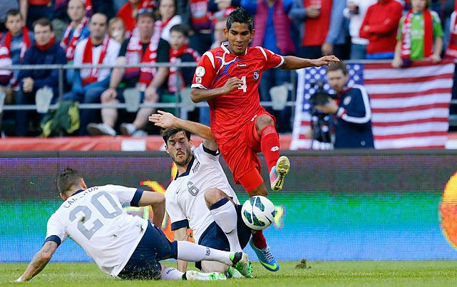 Carlos Rodriguez leaps over U.S. defenders Geoff Cameron (20) and Brad Evans.
