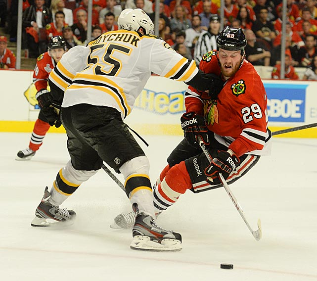 The Blackhawks' Bryan Bickell attempts to skate by Bruins defenseman Johnny Boychuk, who logged 41:37 of ice time during the game.
