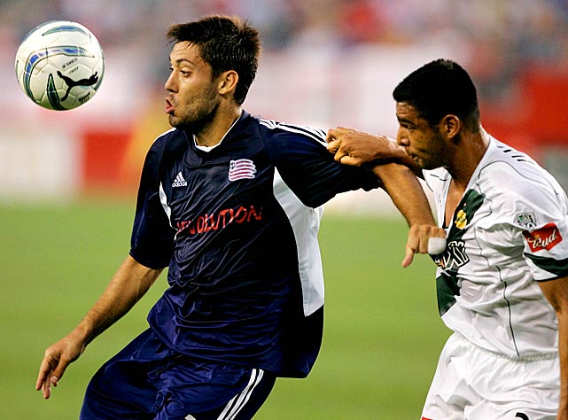 Los Angeles Galaxy forward Michael Umana hangs onto Clint Dempsey while battling for possession.
