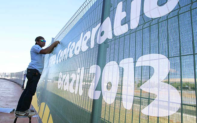 A worker sets up an advertisement banner at the National Stadium ahead of the Confederations Cup in Brasilia, Brazil.
