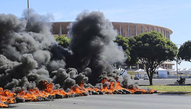 Protesters burn tires in front of the Mane Garrincha stadium, site of Saturday's Brazil-Japan match.