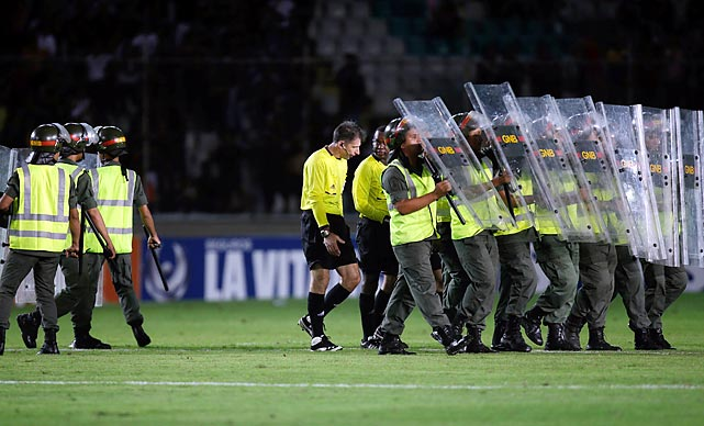 Referees from Brazil are escorted by National Guard soldiers after the Uruguay-Venezuela match in Puerto Ordaz, Venezuela, where they seem to take this sport rather seriously. Uruguay won, 1-0.