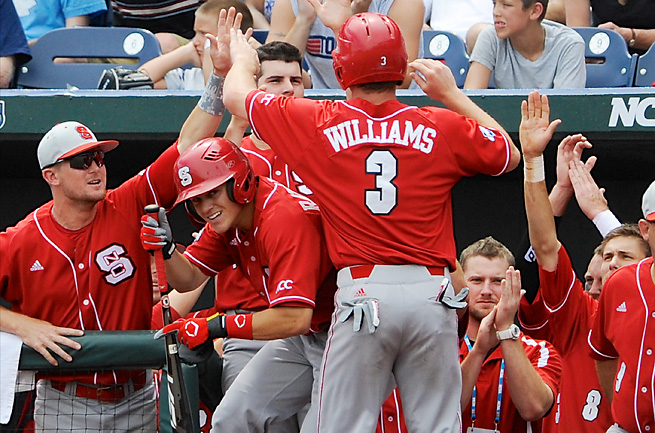 Brett Williams is congratulated by the Wolfpack dugout after scoring during NC State's rout of its rival.