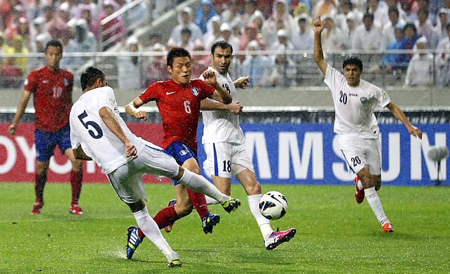 South Korea's Lee Myung-ju (center) fights for the ball against Uzbekistan players in a match last Tuesday.
