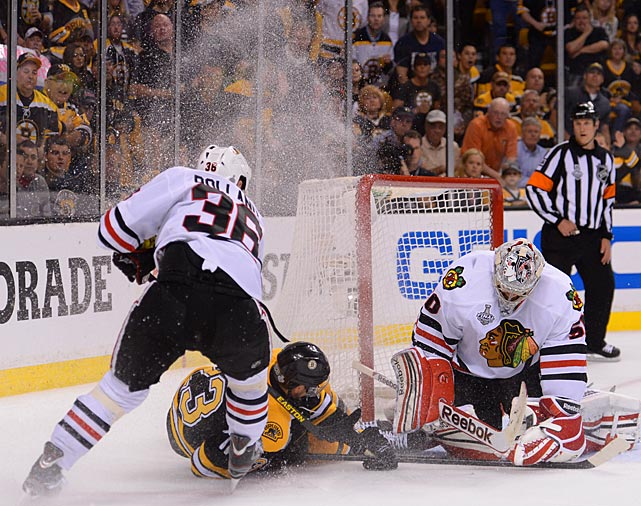 Blackhawks goalie Corey Crawford covers the puck as the Bruins' Chris Kelly slides into the net under pressure from Dave Bolland, who had a shaky game. The Hawks' center lost the puck on a play that led to Boston's first goal. He later took a tripping penalty and was just leaving the box when the Bruins struck again. To cap it all off, he finished the game 1-for-7 in face-offs.