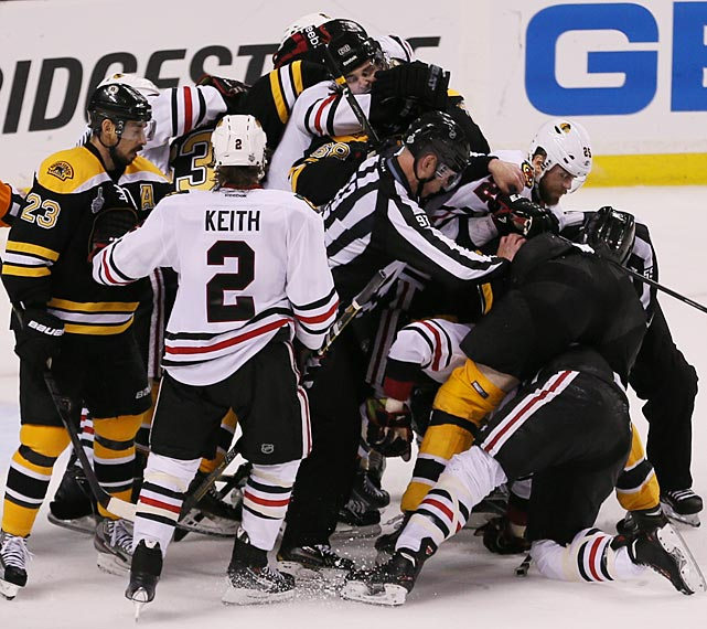 Boston's Chris Kelly (23) and Chicago's Duncan Keith look on as a scrum breaks out in the final minute.
