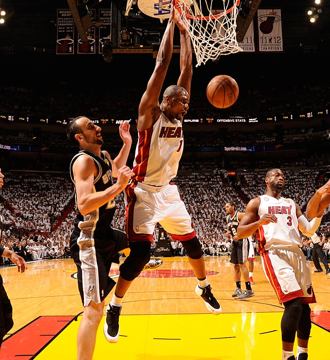 Miami's Chris Bosh hangs onto the rim after a dunk.