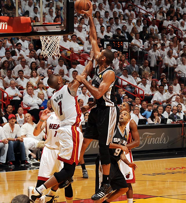 The Spurs' Tim Duncan finishes with a one-handed slam over the Heat's Chris Bosh.