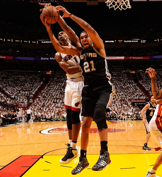 San Antonio's Tim Duncan (21) and Miami's Chris Bosh battle for a rebound. Duncan grabbed 17 boards on the evening, but it was Bosh's crucial rebound in the waning seconds of regulation that led to Ray Allen's game-tying three-pointer.