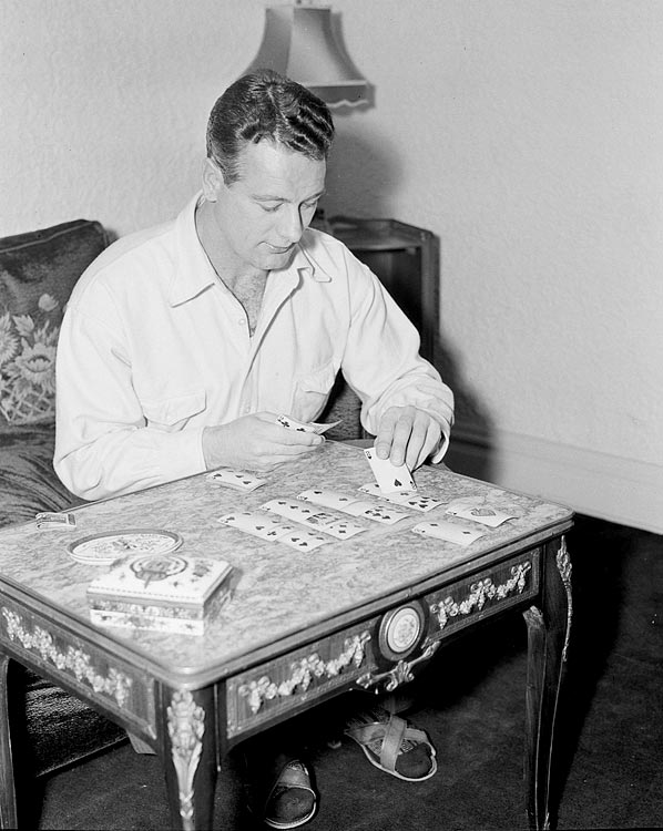 Sitting at home, Lou Gehrig plays a game of cards, in Dec. 1936.