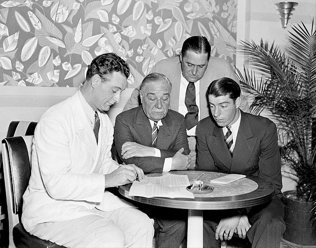 Gehrig signs a contract on March 21, 1937, for $36,000 as (left to right) Jake Ruppert, manager Joe McCarthy, and Joe DiMaggio watch.