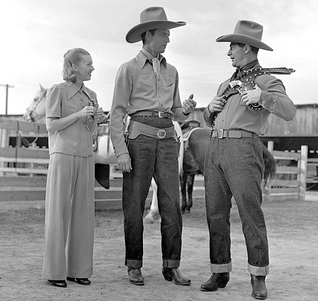 The Yankees first baseman starred as himself in the 1938 western film <italics>Rawhide</italics> -- his only feature film appearance. Here Gehrig, Smith Ballew, and Evalyn Knapp attempt to figure out how to wear a shoulder and belt holster.