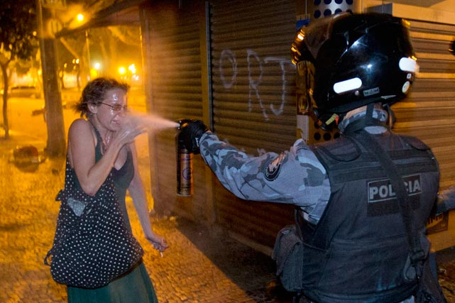 A member of the Brazilian military police peppers sprays a protester during a demonstration in Rio de Janeiro. Widespread demonstrations in Brazil -- many of them outside of soccer stadiums -- have quickly become the main story of the 2013 Confederations Cup. With Brazil preparing to also host the 2014 World Cup and the 2016 Summer Olympics in Rio, tens of thousands of Brazilian protesters have displayed their anger against the government for the poor quality of public services that they receive.