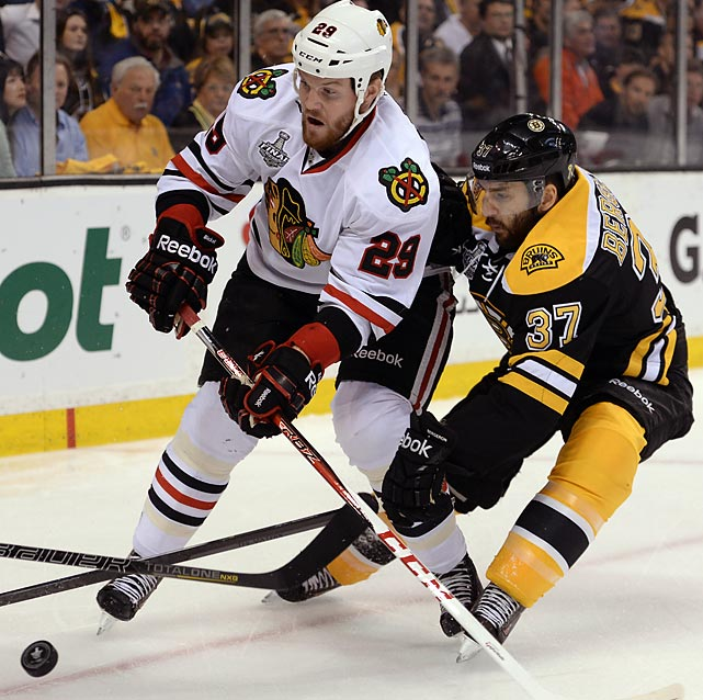 Bryan Bickell battles Patrice Bergeron, who had another big game with two goals -- his eighth and ninth of the postseason.