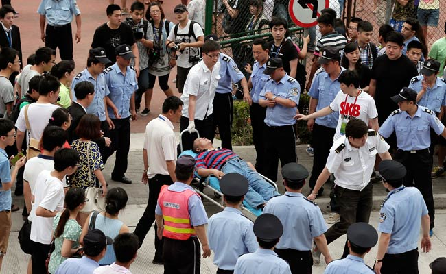 An injured man is carried to an ambulance after a stampede occurred during David Beckham's visit to Shanghai.