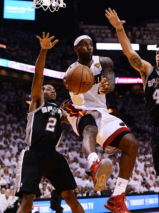 Guarded by the Spurs' Kawhi Leonard (left) and Danny Green, LeBron James looks to pass.