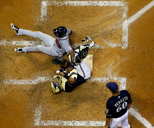 Milwaukee Brewers catcher Martin Maldonado holds onto the ball as the Atlanta Braves' B.J. Upton is thrown out at home on a suicide squeeze in the fifth inning. The Brewers won 2-0.