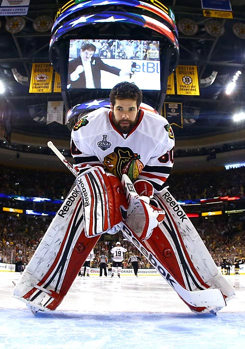 Corey Crawford leans over on the ice during the national anthem prior to Game Six. Crawford stopped 23 of 25 Bruins' shots to lead the Chicago Blackhawks to a 3-2 victory and earn his first NHL championship as a starting goaltender.