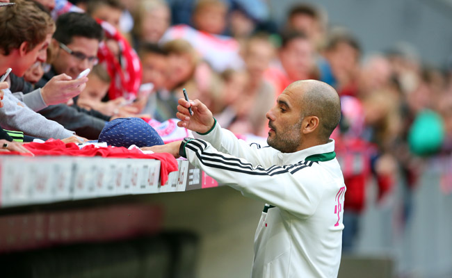 Pep Guardiola signs autographs for Bayern Munich fans who attended Guardiola's first training session.