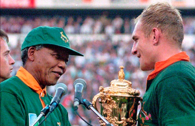 Nelson Mandela hands the 1995 Rugby World Cup trophy to South African captain Francios Pienaar.