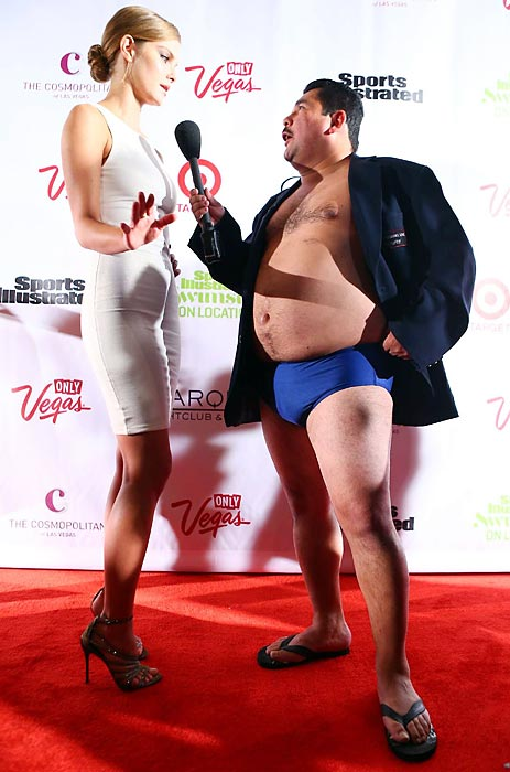 Here we have Guillermo (right), who clearly dreams of gracing the cover of next year's SI Swimsuit Issue, asking a model for tips on how to maintain his buoy-ish figure during the gala bash at The Cosmopolitan of Las Vegas.