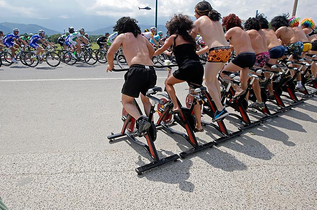 Spectators on stationary bikes cheer as the pack of riders passes in Ghisonaccia during the first stage of the 100th edition of the Tour de France.