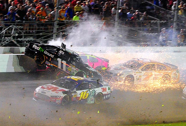 Denny Hamlin (11) hits the wall as he wrecks with A.J. Allmendinger (back) and Dave Blaney (7), as Greg Biffle (16) drives past during the Sprint Cup race at Daytona International Speedway on July 6.