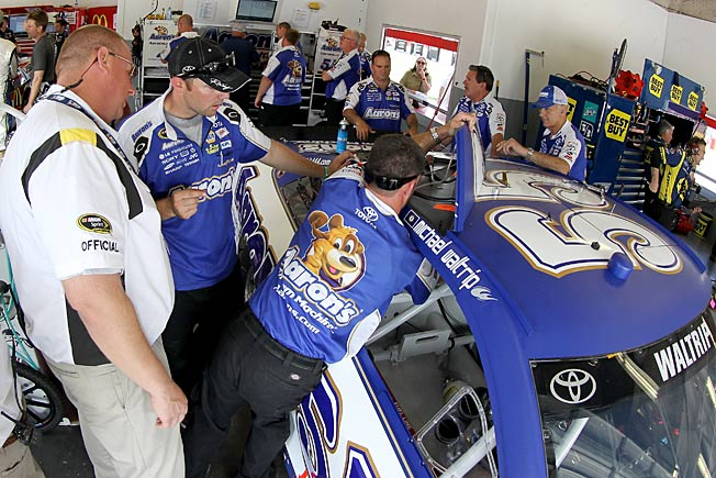 Crew members work on the roof flaps of Michael Waltrip's Toyota during practice at Daytona on July 4.