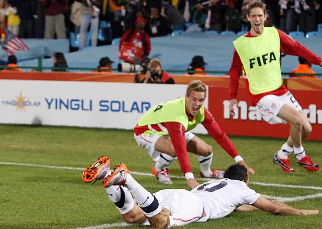 Donovan dives toward the corner flag, where teammates Stuart Holden (left) and Clarence Goodson celebrate after Donovan's stoppage-time goal propelled the United States to the knockout stage of the 2010 World Cup.