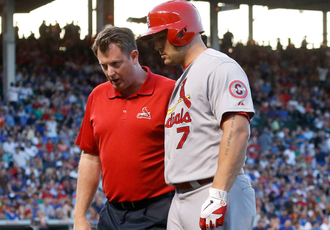 The Cardinals' trainer helped Matt Holliday off the field after he suffered a hamstring injury.