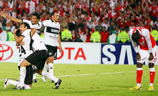 Olimpia players (white) celebrate their team's victory over Independiente Santa Fe on July 9 in Bogoto, Colombia.