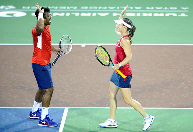 Martina Hingis high-fives partner Leander Paes during their World TeamTennis mixed doubles match.