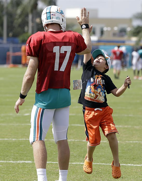 Miami Dolphins quarterback Ryan Tannehill gives a high-five to a jumping Casey Rizzi, 7, of Davie, Fla., after practice.