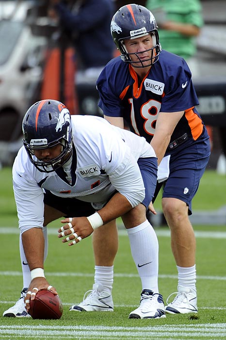 Denver quarterback Peyton Manning takes a snap from center Manny Ramirez during training camp in Englewood, Colo.