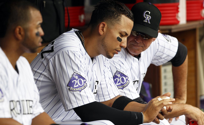 Carlos Gonzalez shows his injured finger to Rockies bench coach Tom Runnells.